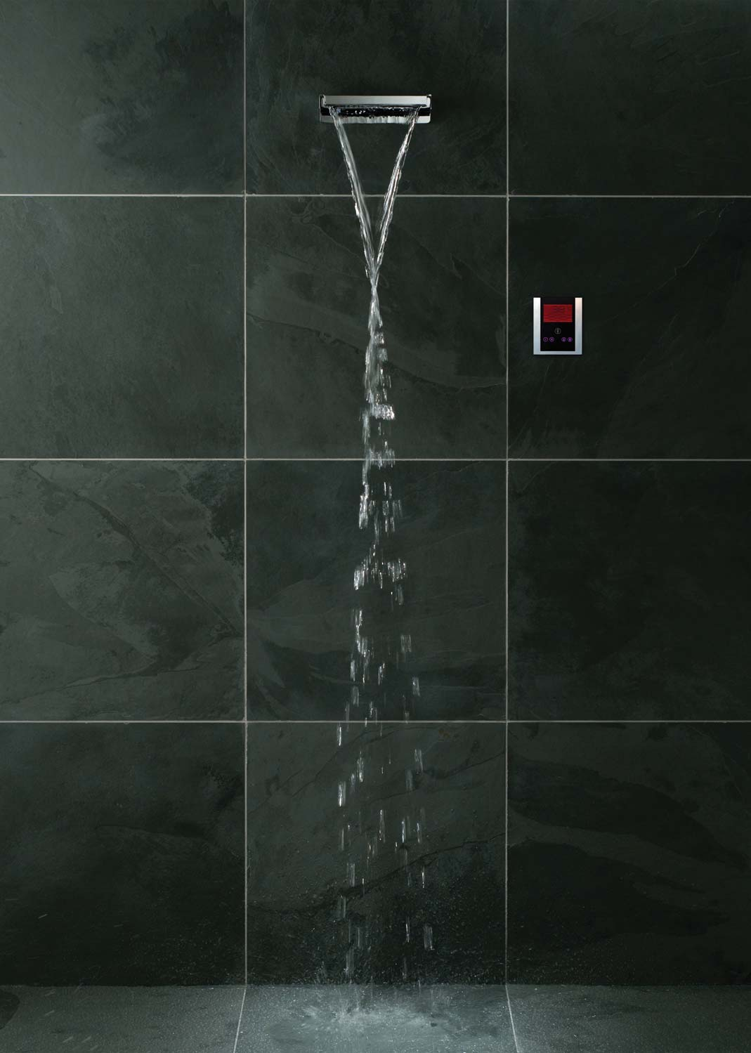 Waterfall overhead shower on a dark slate tiled wall with a digital shower valve and cascading water