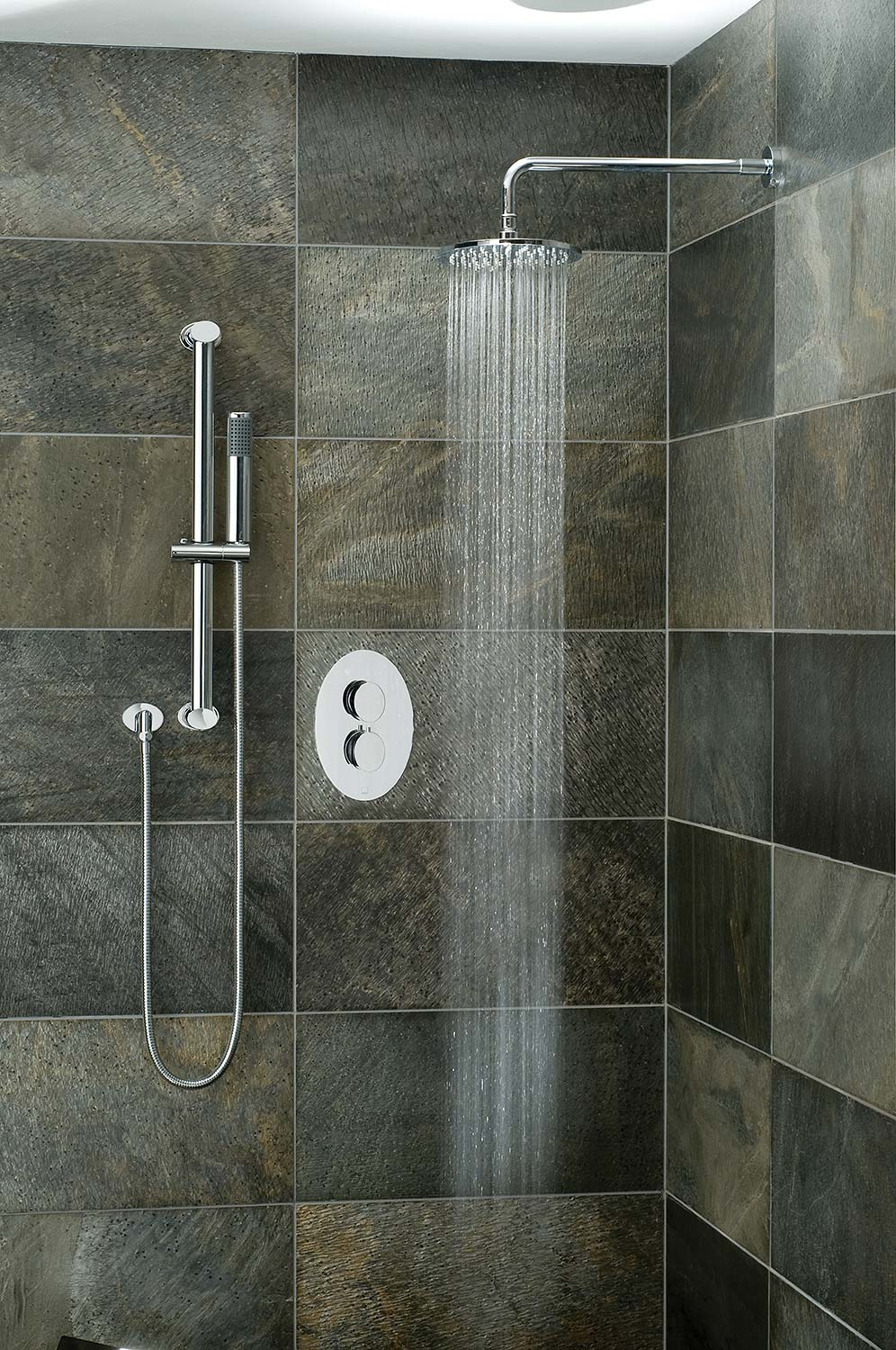 Tiled bathroom with a slide rail shower kit, shower arm and head, and oval thermostatic valve with and water cascading from the shower head