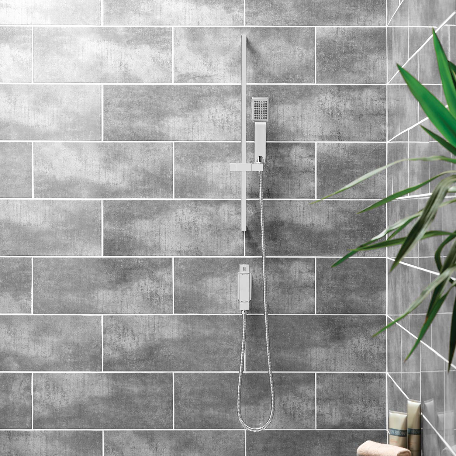 A Slide rail shower kit on a large brown tiled wall with a green plant in the foreground.